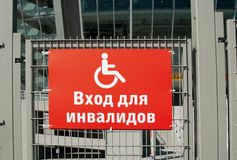Handicap sign. White handicap sign on red background. Stadium sign in Russian: Entrance for handicapped persons only Royalty Free Stock Photo