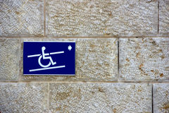 Handicap sign on a wall. Blue handicap sign on a wall showing the way to enter the building for disabled people stock images