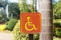 Handicap sign. Wooden wheelchair handicap sign in the garden Royalty Free Stock Photography