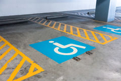 Handicap sign and yellow stripes on cement floor at parking area Royalty Free Stock Image