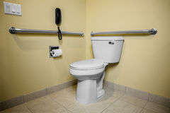 Handicap Toilet Phone. Wall handles help the disabled and handicap use the toilet with easier access. The easy access to the phone will help in case of an Royalty Free Stock Photos