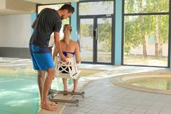 Handicaped woman on a pool lif at a swimming pool stock images