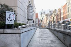 Handicapped Accessible Ramp in Urban Setting. Modern building stone ramp in urban setting for handicapped accessibility use only stock photo