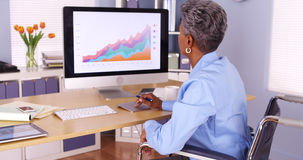 Handicapped African businesswoman working at desk Royalty Free Stock Photos