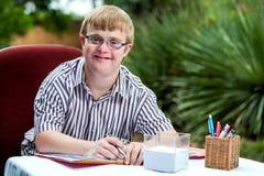 Handicapped boy at desk in garden. Close up portrait of handicapped student wearing glasses at desk in garden stock image
