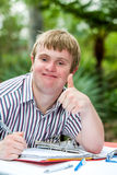 Handicapped boy doing thumbs up at desk outdoors. Close up portrait of handicapped student doing thumbs up at desk outdoors stock photography