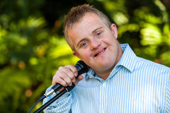 Handicapped boy holding microphone. stock photography