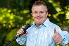 Handicapped boy with microphone doing thumbs up. Royalty Free Stock Photo