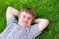 Handicapped boy relaxing on green grass. Close up portrait of handicapped boy laying with hands under head on green grass Stock Photography