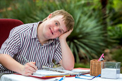 Handicapped boy resting on hand at desk. Stock Images