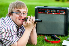 Handicapped boy singing with microphone and amplifier. Close up portrait of handicapped boy singing with microphone and amplifier outdoors royalty free stock images