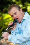 Handicapped boy singing on microphone. Portrait of boy with down syndrome singing on microphone outdoors royalty free stock image