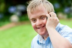 Handicapped boy talking on cell phone. Close up portrait of handicapped boy talking on smart phone outdoors royalty free stock photo