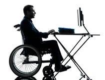 Handicapped business man computing laptop computer  in wheelchai. One handicapped business man computing laptop computer in silhouette studio  on white Stock Photo