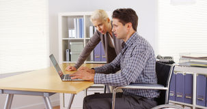 Handicapped businessman and colleague working in the office Royalty Free Stock Photo