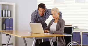 Handicapped businesswoman and colleague working together. In office Royalty Free Stock Photo