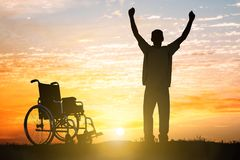 Handicapped Can Walk Again. Silhouette Of Miracle Handicapped Man Walking Again At Sunset royalty free stock photos