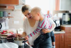 A handicapped down syndrome boy cooking soup with his mother indoors. stock photo