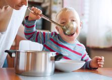 A handicapped down syndrome boy eating soup from a ladle indoors, lunch time. stock images