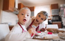 A handicapped down syndrome boy with his mother indoors baking. royalty free stock photography