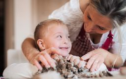 A handicapped down syndrome boy with his mother indoors baking. royalty free stock image