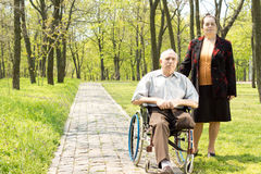 Handicapped elderly man with his wife Royalty Free Stock Photos