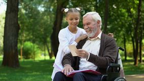 Handicapped grandpa showing to granddaughter family photos telling about granny