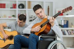 Handicapped guitarist with friend. Handicapped guitarist with a friend Royalty Free Stock Photos