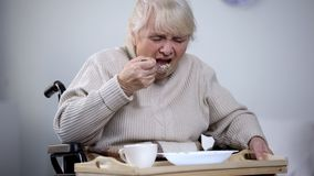 Handicapped lady reluctantly eating dinner in medical center, inappropriate care stock image