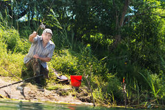 Handicapped man casting his line when fishing Stock Photo