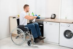 Handicapped man cleaning induction stove Royalty Free Stock Photo