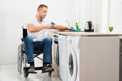 Handicapped man cleaning induction stove Stock Photos