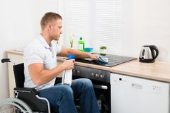 Handicapped man cleaning induction stove Stock Photography