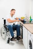Handicapped man cleaning induction stove Royalty Free Stock Images