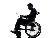 Handicapped man computing laptop computer  in wheelchair silhoue Royalty Free Stock Photo