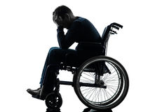 Handicapped man head in hands in wheelchair silhouette. One handicapped man head in hands in silhouette studio  on white background Royalty Free Stock Photo