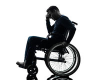 Handicapped man head in hands in wheelchair silhouette Stock Photos