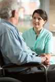 Handicapped man and his nurse. Handicapped senior men and his smiling nurse stock images