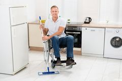 Handicapped man mopping floor Stock Image