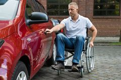 Handicapped man opening door of a car Stock Image