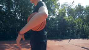 Man with prosthetic arm holds a ball. Futuristic concept. Handicapped man stands on a basketball court with a ball in hands
