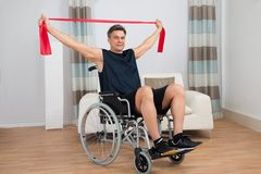 Handicapped man on wheelchair exercising with resistance band Royalty Free Stock Image