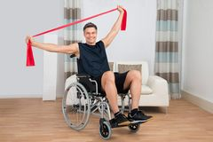 Handicapped man on wheelchair exercising with resistance band Stock Photography