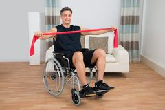 Handicapped man on wheelchair exercising with resistance band Royalty Free Stock Photo
