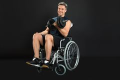 Handicapped man on wheelchair working out with dumbbell Royalty Free Stock Photography