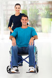 Handicapped man wife. Handicapped men sitting on wheelchair with caring wife at home Royalty Free Stock Photography