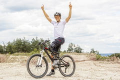 Handicapped mountain bike raising up arms. Shot of young  mountain bike rider with leg prosthesis raising up his arms Stock Images