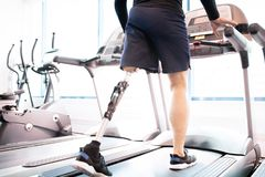 Handicapped Muscular Man Running on Treadmill. Low angle portrait of unrecognizable muscular man with prosthetic leg using walking on treadmill while working out stock photos