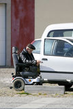 Handicapped old man. Trying to get into the car in a parking lot. Real life shot depicting handicapped people difficulties to live a normal life. Shot taken in Royalty Free Stock Photo