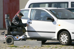 Handicapped old man. Trying to get into the car in a parking lot. Real life shot depicting handicapped people difficulties to live a normal life. Shot taken in royalty free stock image